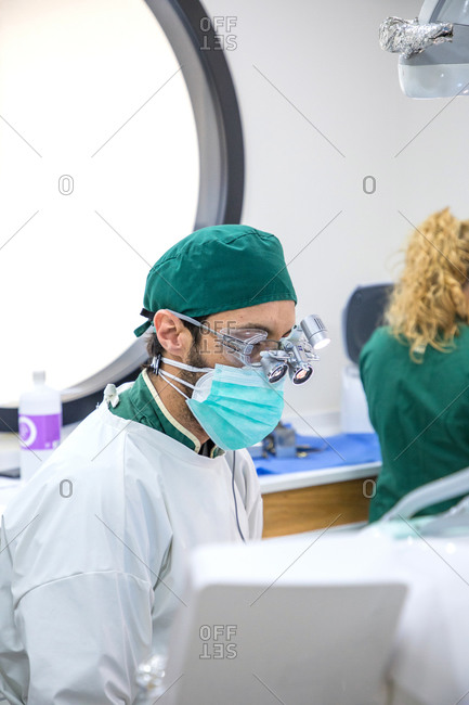 Low angle of focused male dentist in binocular glasses and uniform working in modern dental clinic