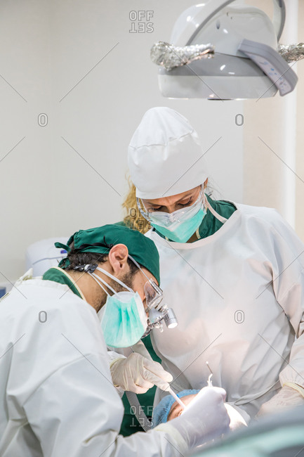 Dentists in masks and uniform operating patient lying in dental chair in bright modern clinic