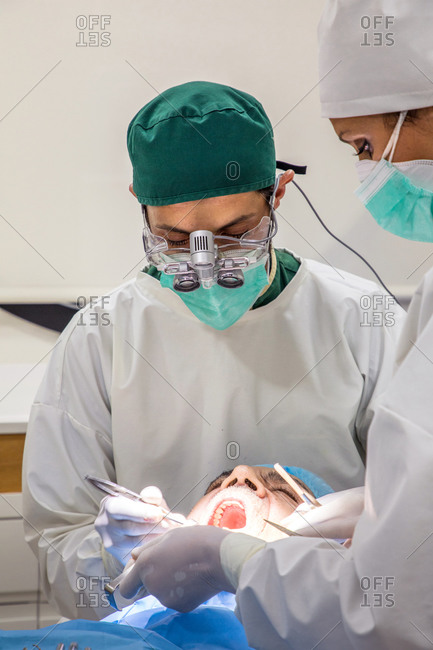 Focused professional dentist examining teeth of patent with dental instruments with help of assistant in bright room in clinic