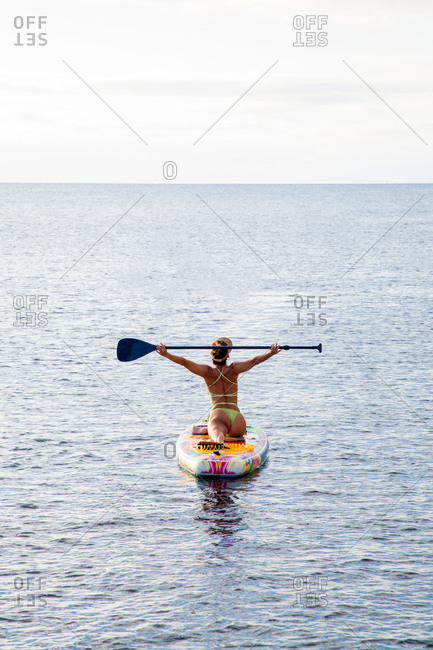 Active female surfer in swimwear holding paddle in raised hand while standing on paddle board floating in sea water near coast