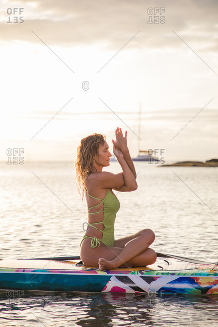 Full body side view of slender young female in swimsuit doing Cow Face yoga asana with Eagle pose arms while floating on paddle board at sunset