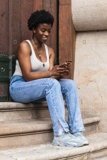 Cheerful curly haired African American female browsing social media in mobile phone and smiling brightly