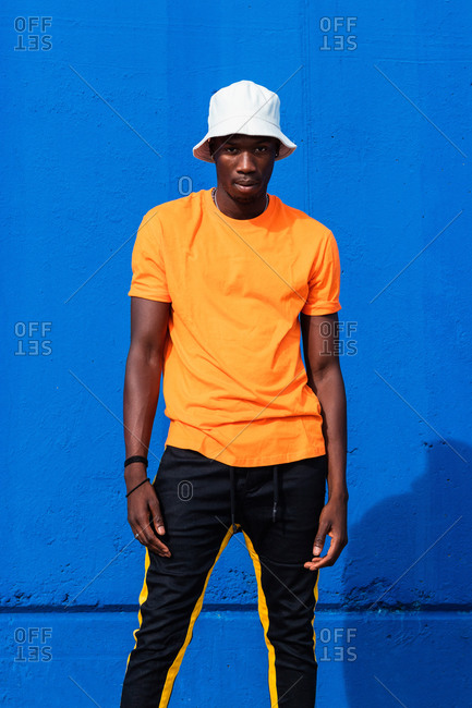 Young African American male in bright yellow t shirt and sportive pants posing while standing against blue wall
