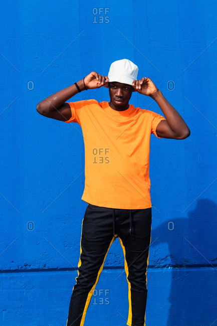 Young African American male in bright yellow t shirt and sportive pants adjusting white cap while standing against blue wall