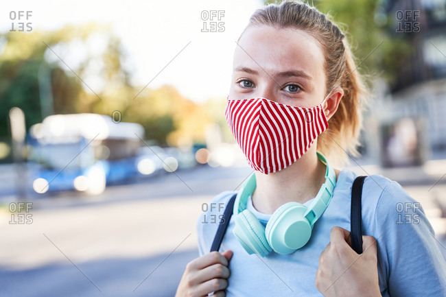 Positive millennial female student in textile protective mask and with backpack and headphones looking at camera while standing against blurred urban background