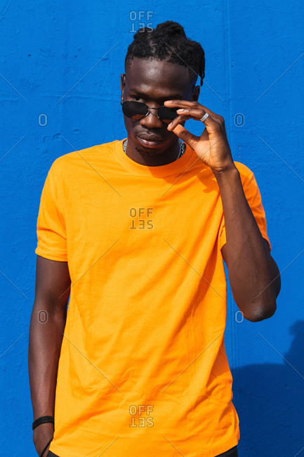 Serious young African American guy in bright yellow t shirt and trendy sunglasses looking away against blue background