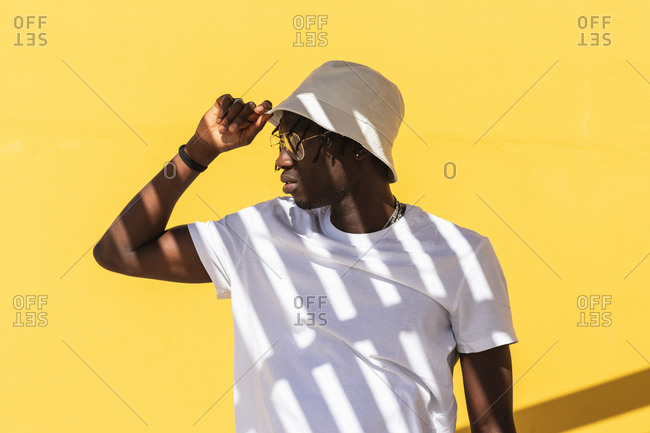 Modern hipster African American guy with striped shadow on white t shirt wearing sunglasses and panama hat and looking away while standing against yellow wall