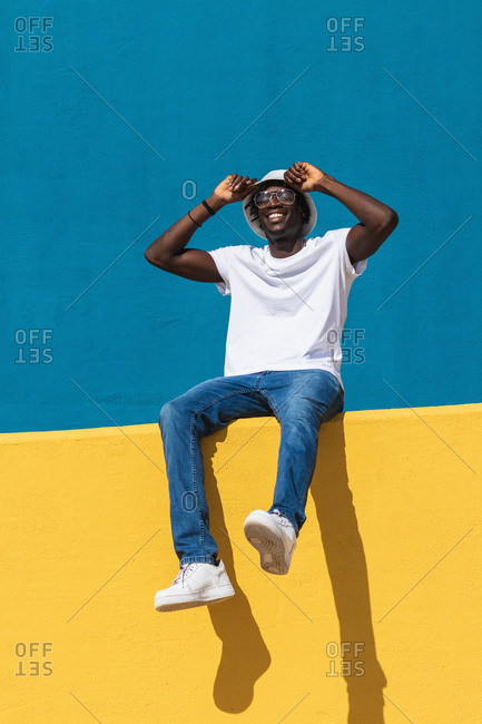 Low angle full body of optimistic young black male in casual outfit with panama hat and sunglasses smiling happily while siting on bright colorful fence and enjoying sunny summer day