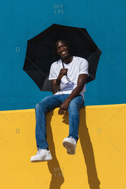 Optimistic young black male in casual outfit with panama hat and sunglasses smiling happily while holding an umbrella siting on bright colorful fence and enjoying sunny summer day