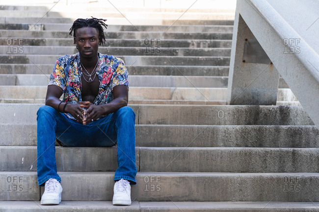 Low angle full body of serious African American male in colorful shirt and jeans with sneakers sitting on stone steps and looking at camera on urban street