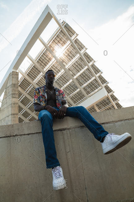 From below full body of stylish black guy in trendy colorful shirt and jeans with white sneakers sitting on concrete fence against modern city building