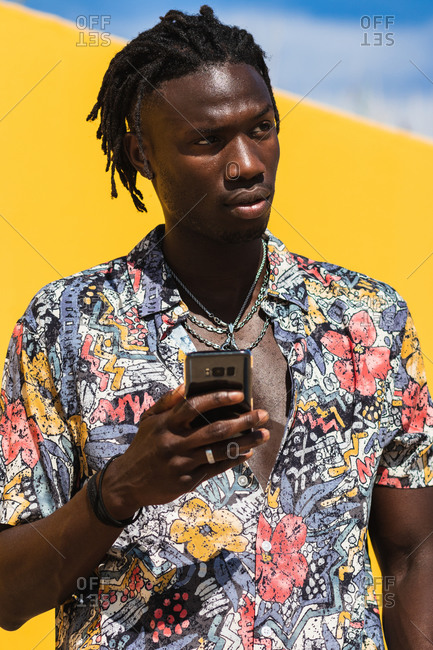 Confident young hipster African American male with dreadlocks wearing trendy summer shirt with floral print and jeans using mobile phone and looking way against yellow background