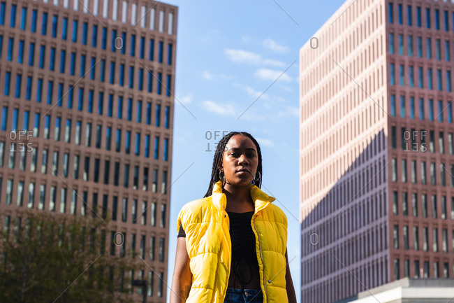 Low angle of young African American female in stylish yellow waistcoat standing against high rise buildings and cloudy blue sky on city street