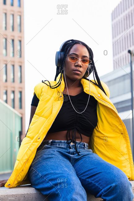 Young black female in trendy waistcoat and sunglasses with headphones and enjoying favorite music looking at camera in downtown