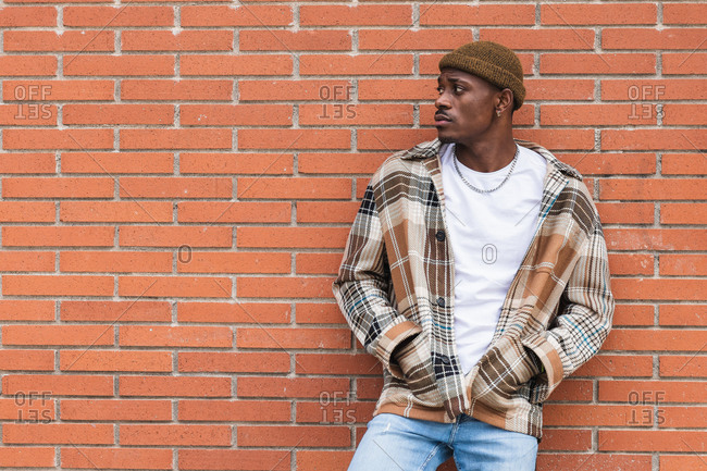 Young African American guy in checkered shirt and trendy hat frowning and looking away while standing against brick wall on city street