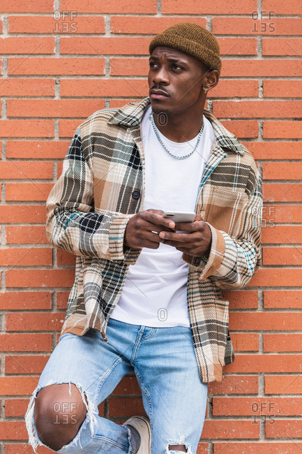 African American guy in casual outfit frowning and browsing social media on smartphone while leaning on brick wall on street