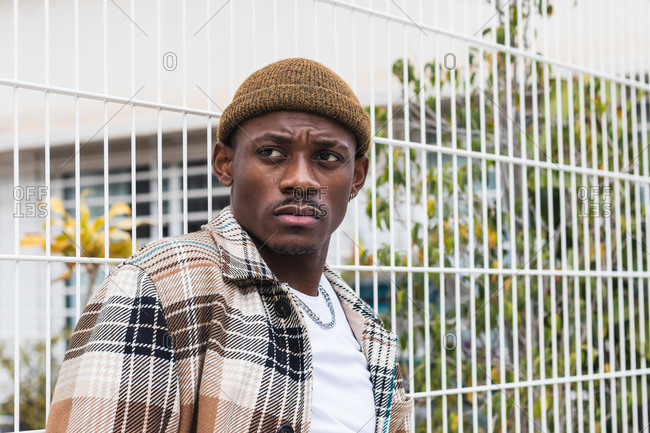 Young black man in stylish checkered shirt and hat leaning on net fence and looking away on modern city street