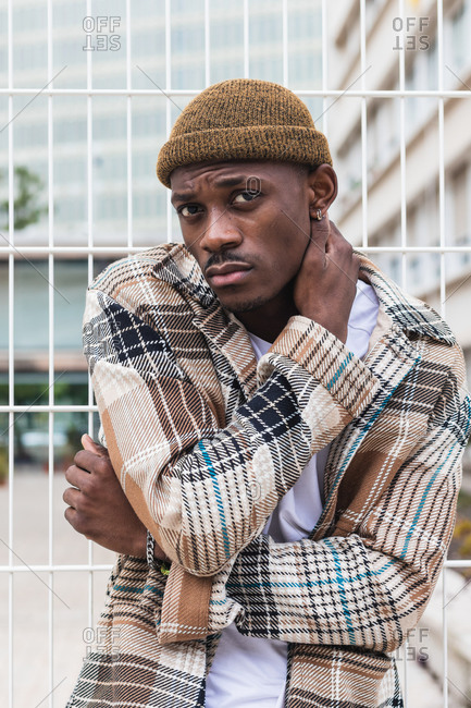 Young black man in stylish checkered shirt and hat leaning on net fence and looking at camera on modern city street