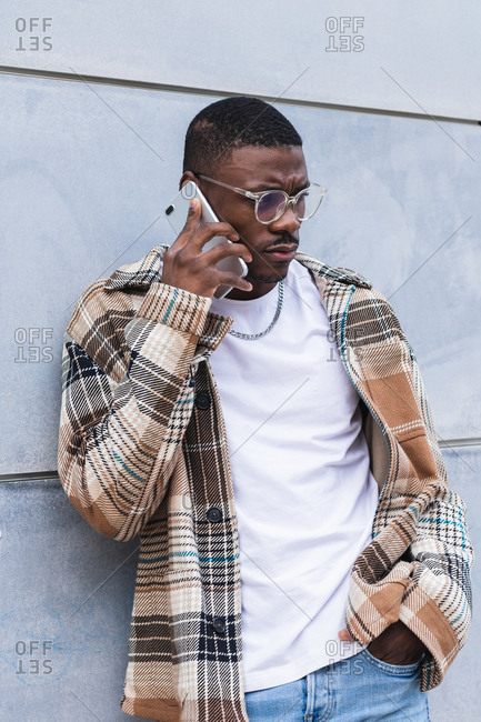 African American man in trendy checkered shirt and glasses talking while leaning on wall of modern building on city street
