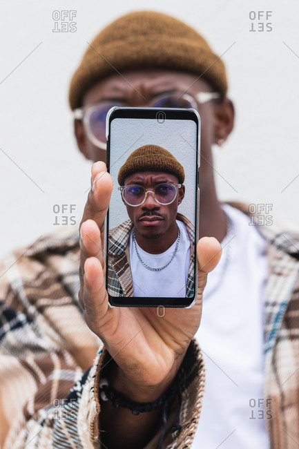 Soft focus of African American male demonstrating mobile phone with selfie against gray wall on city street
