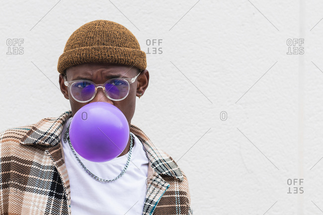 Young black male in stylish hat and glasses looking at camera and blowing violet balloon against gray wall