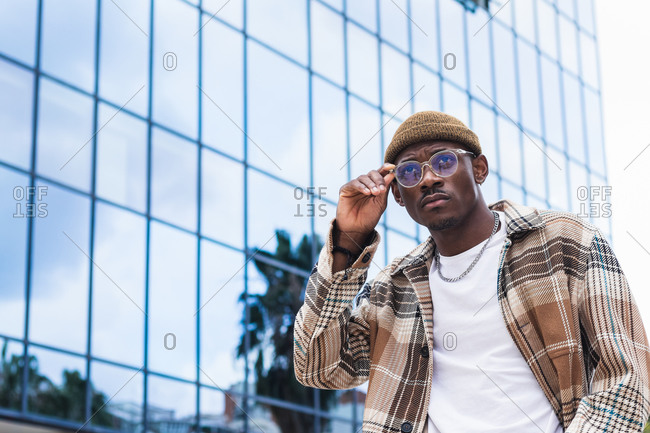 Young African American male in stylish checkered shirt looking away and walking on city street outside modern glass building