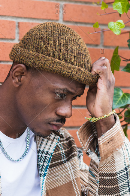 Young African American guy in checkered shirt and trendy hat frowning and looking down while standing against brick wall on city street