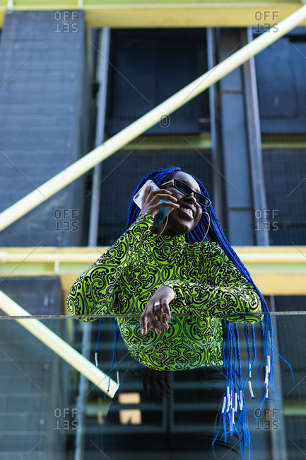 From below confident African American female with blue hair and in vivid clothes leaning on glass fence speaking on smartphone in city