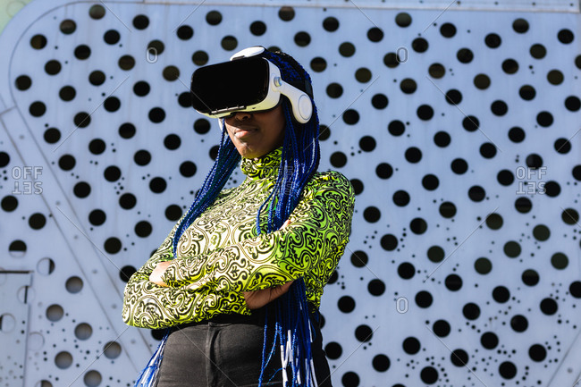 Side view of African American female with blue hair standing in street in VR goggles while experiencing virtual reality