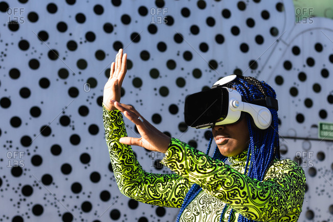 Side view of African American female with blue hair standing in street in VR goggles while experiencing virtual reality and touching air