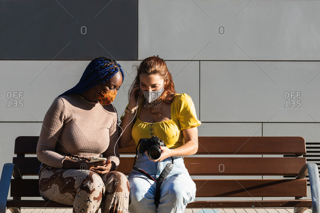 Delighted diverse female friends listening to music and looking through taken photos on photo camera on street