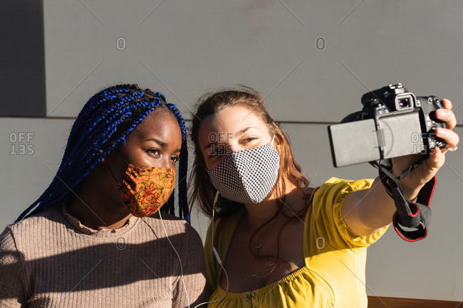 Smiling multiracial female friends in masks standing on street and taking selfie on photo camera during coronavirus pandemic