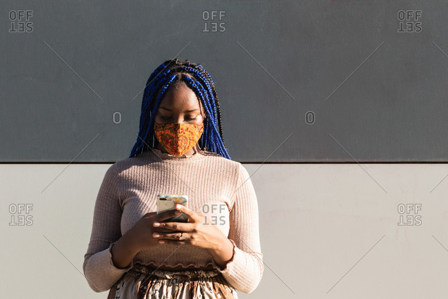 African American female with blue braided hairstyle and in protective mask standing on street and browsing smartphone during coronavirus pandemic in city