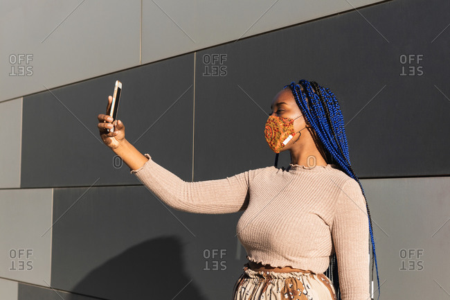 Determined ethnic female with blue braids and in casual clothes standing on street in protective mask and taking self portrait on smartphone during coronavirus outbreak