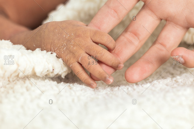 Crop unrecognizable woman hand holding tiny newborn baby hand