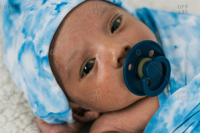 Tranquil adorable newborn baby lying wrapped on blue cozy blanket using pacifier