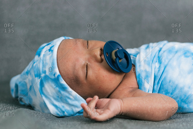 Tranquil adorable sleepy newborn baby lying wrapped on blue cozy blanket using pacifier