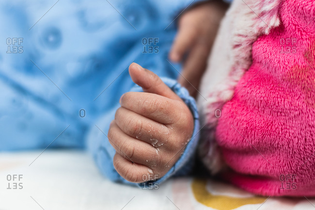 Cropped unrecognizable newborn baby lying on big toy on cozy blanket