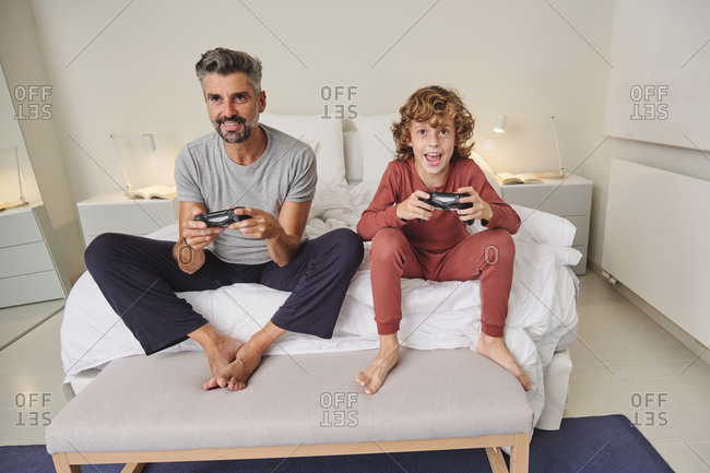Excited man and boy with joysticks playing video games at home while having fun and spending time together