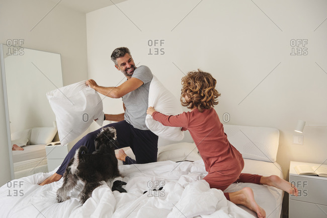 Playful father and son fighting on bed with soft pillows while jumping and having fun