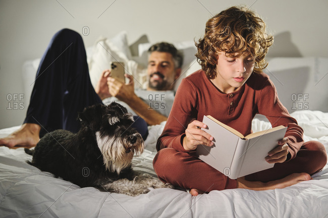 Focused kid reading interesting book while sitting on bed with father and cute dog