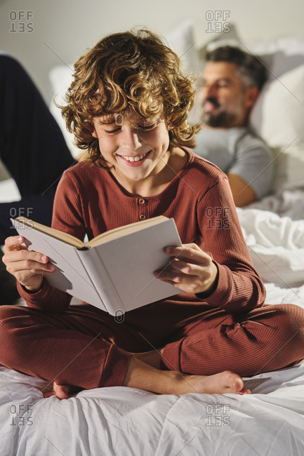 Focused kid reading interesting book while sitting on bed with father
