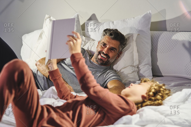 Peaceful man and boy lying on bed and reading interesting story in book together
