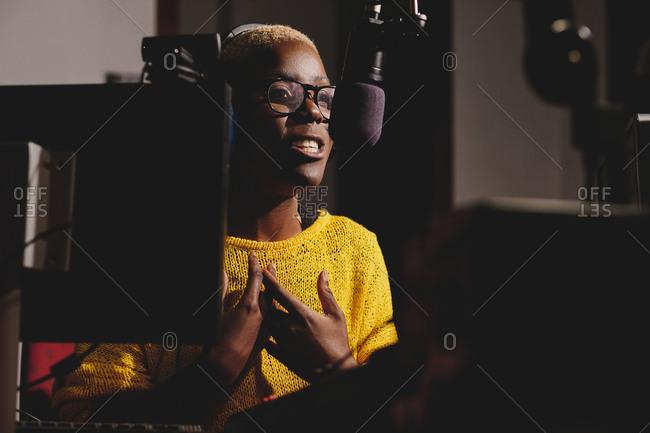 Side view of African American female radio host working in dark broadcast studio and speaking in microphone