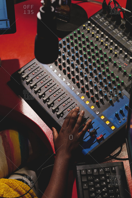 From above of unrecognizable ethnic female radio host using mixing console while working in broadcast studio