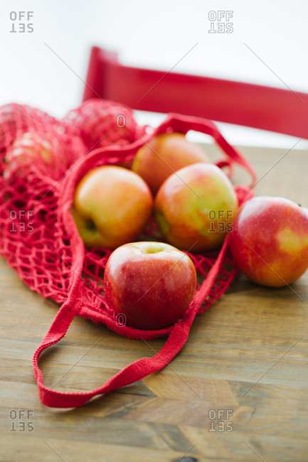 Top view of fresh apples in cotton eco friendly sacks placed on wooden table