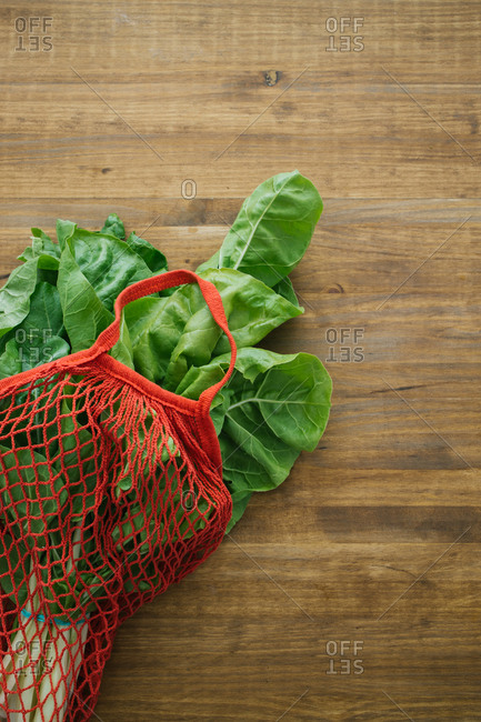 Top view of fresh vegetable in cotton eco friendly sacks placed on wooden table