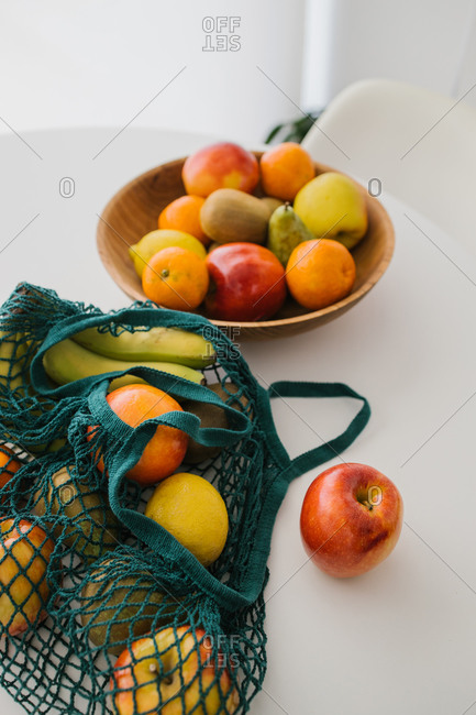 Top view of assorted fresh fruit in cotton eco friendly sacks placed on table