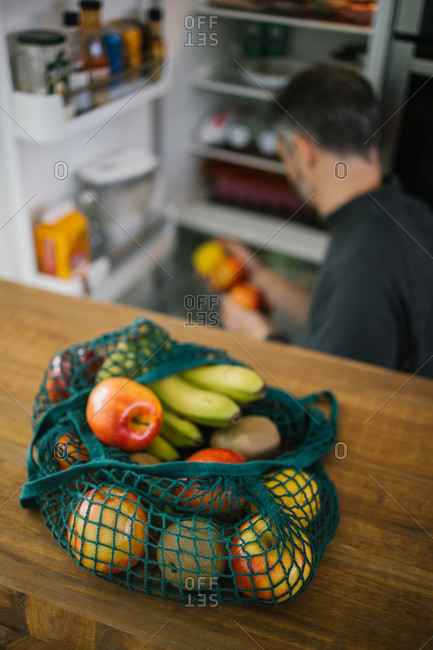 High angle of eco friendly cotton sack with ripe fruits placed on table in kitchen on background of crop person