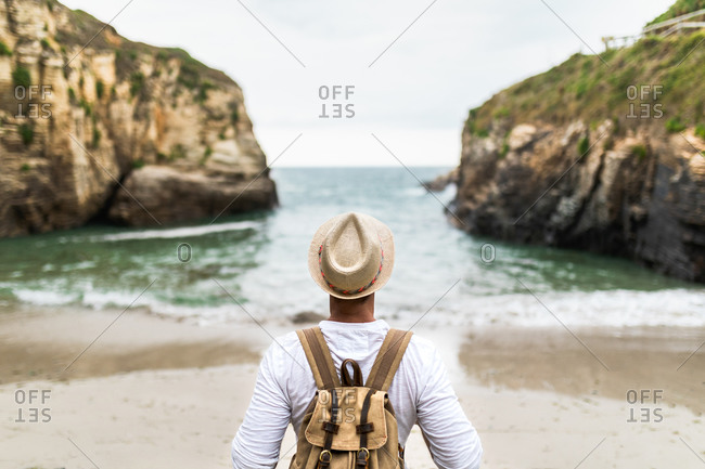 Back view of anonymous male traveler standing on sandy coast enjoying freedom during summer vacation near sea
